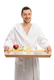 Young man in bathrobe holding tray with fruit, drink and cereal royalty free stock image