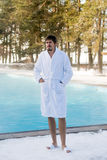 Young man in bathrobe near outdoor swimming pool at winter Royalty Free Stock Images