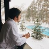 Young man in bathrobe staying at balcony in winter and looking at swimming pool. At snowly resort royalty free stock photo