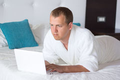 Young man in bathrobe using laptop in hotel room Stock Image