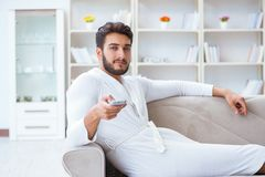 Young man in a bathrobe watching television at home on a sofa co. Uch Royalty Free Stock Image