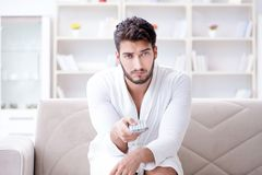 Young man in a bathrobe watching television at home on a sofa co. Uch Stock Images