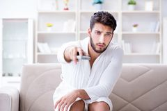 Young man in a bathrobe watching television at home on a sofa co. Uch Royalty Free Stock Images