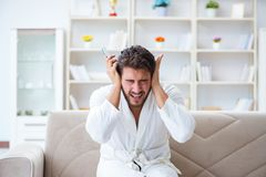 Young man in a bathrobe watching television at home on a sofa co. Uch Stock Photos