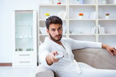 Young man in a bathrobe watching television at home on a sofa co. Uch Royalty Free Stock Photo
