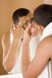 Young man in the bathroom's mirror cleaning his skin Stock Photography