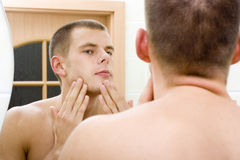 Young man in the bathroom's mirror after shave. Reflexion of young man in the bathroom's mirror after shave Stock Photo