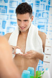 Young man in the bathroom's mirror with shave foam on hand Royalty Free Stock Images