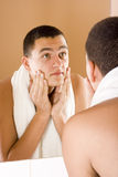 Young man in the bathroom's mirror after shaving Stock Photography