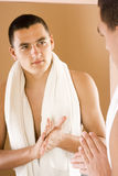 Young man in the bathroom's mirror using cream Stock Image
