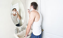 Young Man in Bathroom Shaving Royalty Free Stock Image