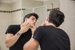 Young Man in Bathroom Squeezing a Spot Royalty Free Stock Photo