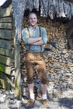 Young man in bavarian lederhosen in front of firewood Royalty Free Stock Image