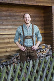 Young man in bavarian lederhosen in front of firewood Stock Image