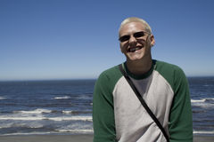 Young man at the beach. A young Caucasian male in sunglasses at the beach Stock Photos