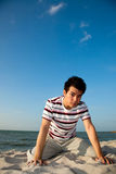 Young man by the beach. Squatting young man relaxing at the beach Stock Images