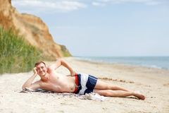 A young man at the beach background. A smiling guy lying on the sand near the blue ocean. Summer concept. Copy space. royalty free stock images