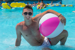Young Man with Beach Ball Lounging in Pool. Young Man Posing in Shallow End of Resort Swimming Pool Holding Striped Beach Ball and Wearing Sunglasses Royalty Free Stock Images