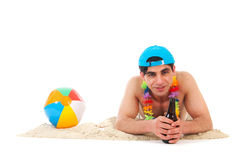 Young man at the beach drinking beer. Young man laying at the beach drinking beer Stock Images