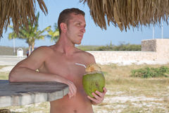 Young man on the beach drinking from coconut Royalty Free Stock Image