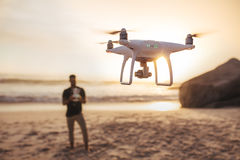 Young man on the beach flying a drone stock image