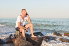 Young man on the beach with a phone. Young man sitting on a rock by the sea and talking on the phone Stock Photo