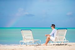 Young man on the beach rest on the sunbed alone outdoor. Young man on the beach rest on the sunbed alone Stock Photos