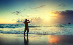 Young man on the beach take photo Royalty Free Stock Photo