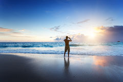 Young man on the beach take photo on phone Stock Images