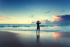 Young man on the beach take photo on phone Stock Photo