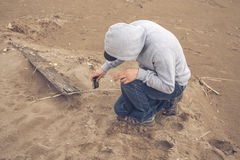Young man on the beach wearing a hoodie and a baseball cap Royalty Free Stock Photo