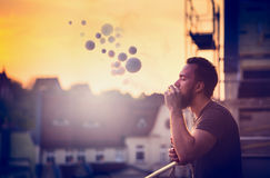 Young man with beard on blurry background sunset sky, making soap bubbles smoke inside with the aid of vape Stock Photo