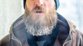 Evaporation from the mouth in winter. Young man with a beard covered with icicles and frozen droplets on the street after exercise. Evaporation from the mouth in stock image