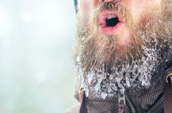 Evaporation from the mouth in winter. Young man with a beard covered with icicles and frozen droplets on the street after exercise. Evaporation from the mouth in stock photos