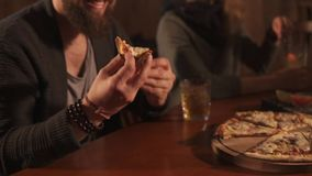Guy is taking pizza from plate in a restaurant during dinner with colleagues. Young man with beard and glasses is bringing piece of pizza from plate to face. He stock video