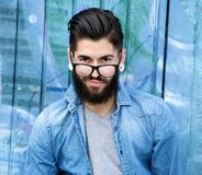 Young man with beard and glasses. Close up portrait of a young man with beard and glasses on graffiti background Stock Photo