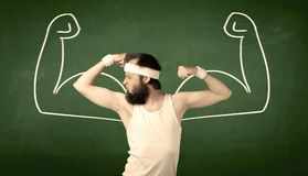 Skinny student wants muscles. A young man with beard and glasses posing in front of green background, imagining how he would look like with big muscles Stock Photo