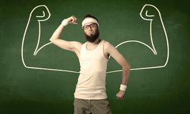 Skinny student wants muscles. A young man with beard and glasses posing in front of green background, imagining how he would look like with big muscles Royalty Free Stock Image