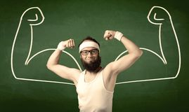 Skinny student wants muscles. A young man with beard and glasses posing in front of green background, imagining how he would look like with big muscles Royalty Free Stock Photos