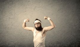 Young male showing muscles. A young man with beard, headstrap and glasses posing in front of blank grey wall background, imagining he has big muscles Stock Image