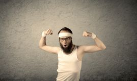 Young male showing muscles. A young man with beard, headstrap and glasses posing in front of blank grey wall background, imagining he has big muscles Stock Photography