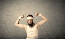 Young male showing muscles. A young man with beard, headstrap and glasses posing in front of blank grey wall background, imagining he has big muscles Stock Photos