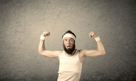 Young male showing muscles. A young man with beard, headstrap and glasses posing in front of blank grey wall background, imagining he has big muscles Royalty Free Stock Photo