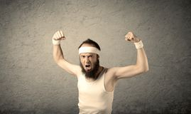 Young male showing muscles. A young man with beard, headstrap and glasses posing in front of blank grey wall background, imagining he has big muscles Royalty Free Stock Photos