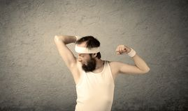 Young male showing muscles. A young man with beard, headstrap and glasses posing in front of blank grey wall background, imagining he has big muscles Stock Images