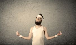 Young male showing muscles. A young man with beard, headstrap and glasses posing in front of blank grey wall background, imagining he has big muscles Royalty Free Stock Image