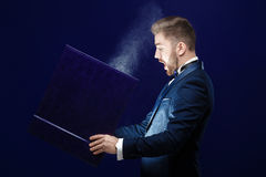Young man with beard holding book and magic light on dark background. Young man with a beard in a tuxedo holding a large book with magic light on dark purple stock photo