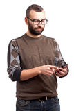 Young man with beard holding cell phone Royalty Free Stock Images
