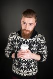 Young man with beard holding a cup of coffee Royalty Free Stock Photos
