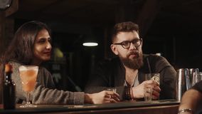 Man and woman communicate with each other at the bar, they drink cocktails. A young man with a beard is holding a glass of beer in his hand, next to him is his stock video